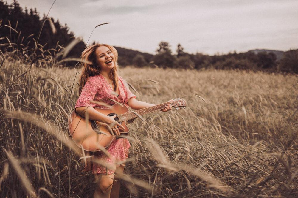 Fotoshooting mit Gitarre lachend